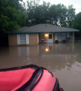 A rescue craft approaches a home in Williamson County during a flood event.